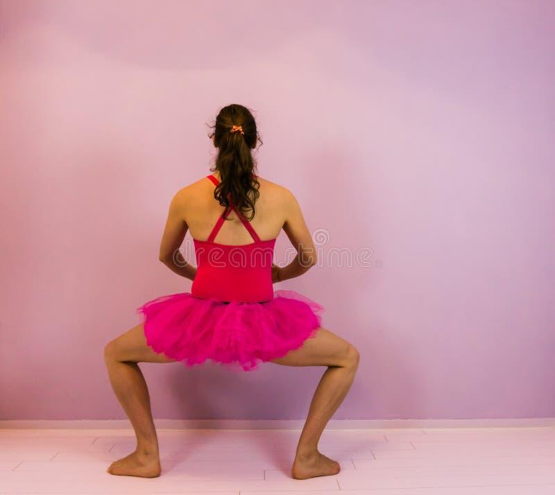执行plie在一件桃红色芭蕾舞短裙,古典芭蕾移动,跳舞的体育的年轻变性女孩的芭蕾舞女演员 图库摄影