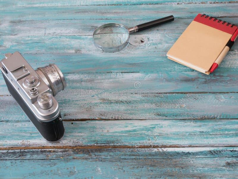 扩大化玻璃、笔记薄和葡萄酒照相机蓝色背景 免版税图库摄影