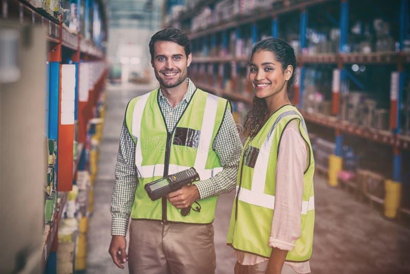 扫描箱子的微笑的仓库工作者画象  免版税库存图片