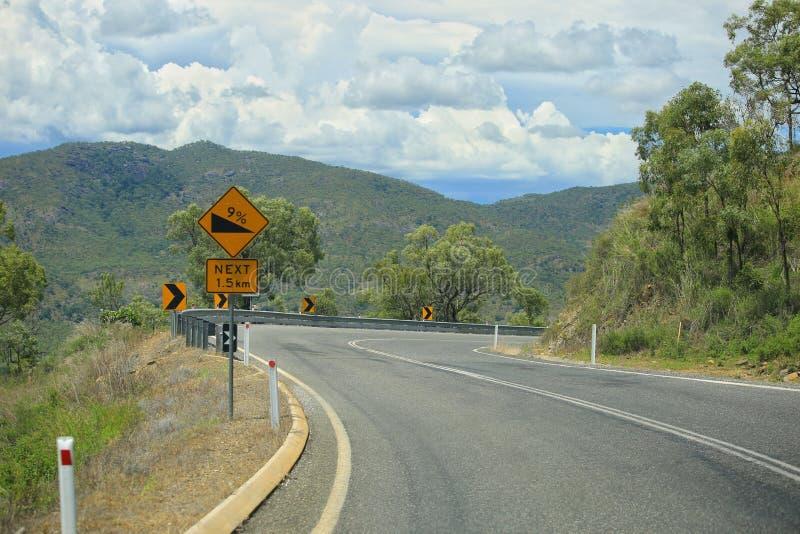 扭转在山的柏油路 黄色路标注意危险轮,蜒蜒 库存图片