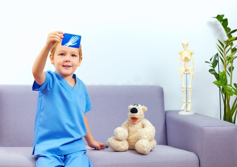 扮演一位医生的逗人喜爱的小孩在办公室 库存照片