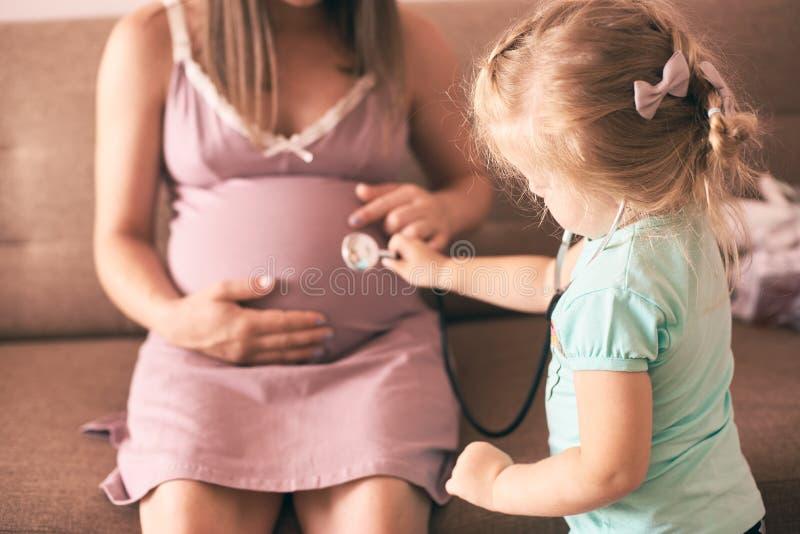 扮演医生和检查怀孕的母亲的逗人喜爱的女儿 图库摄影