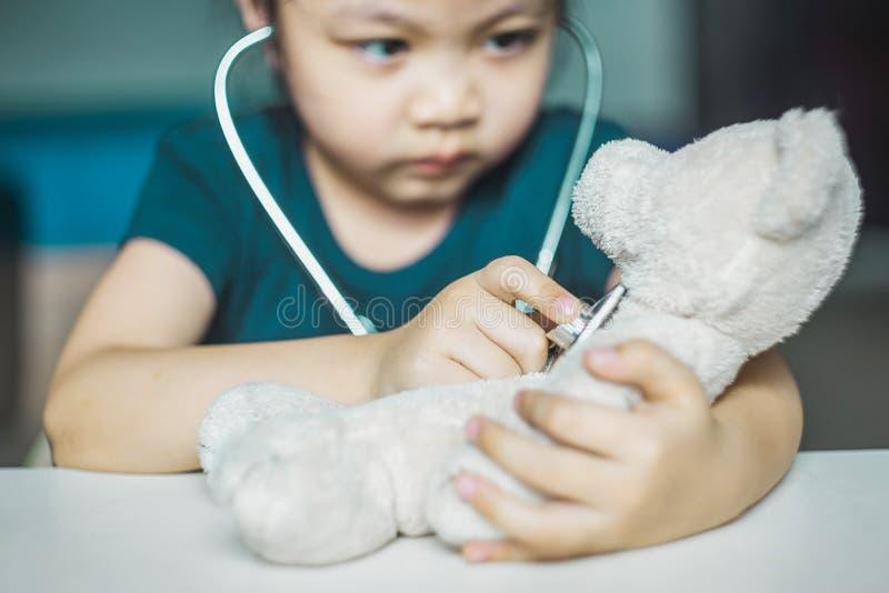 扮演医生或护士有听诊器和锂的逗人喜爱的小女孩 免版税库存图片