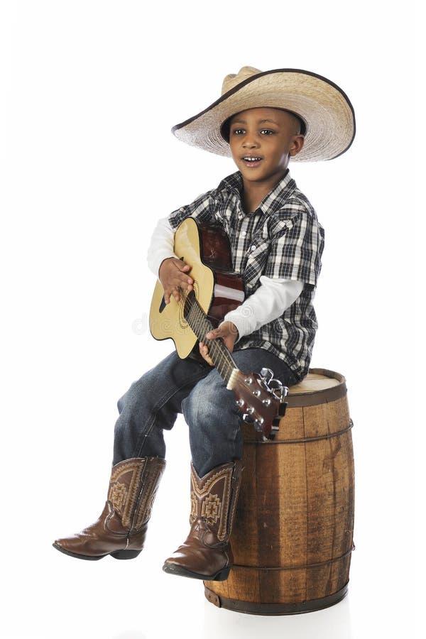 年轻扮演吉他的牛仔 免版税库存照片