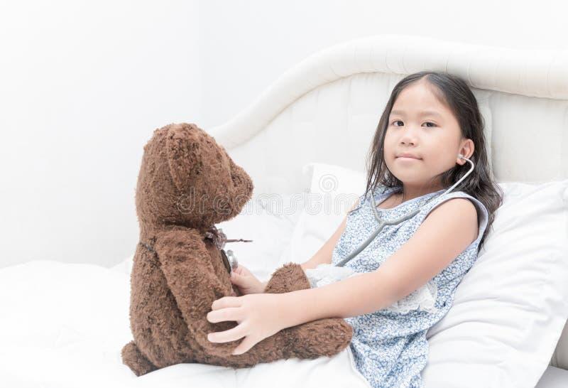 扮演有听诊器和玩具熊的孩子或孩子医生 免版税图库摄影