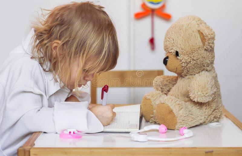 扮演有她的玩具熊的小女孩一位医生 免版税库存图片