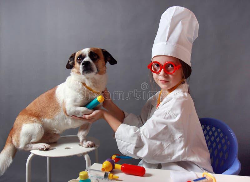扮演有狗的小女孩兽医 免版税库存照片