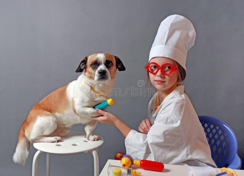 扮演有狗的小女孩兽医 免版税库存图片