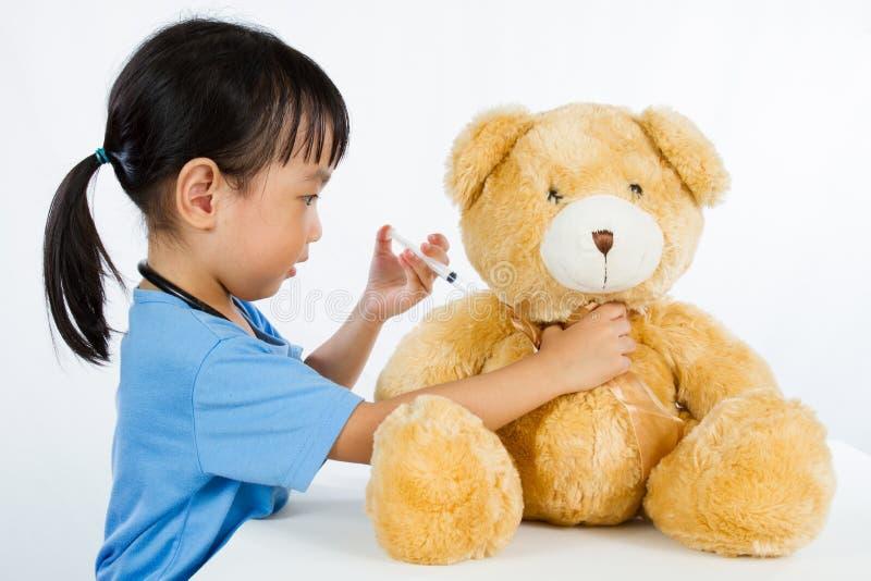 扮演有玩具熊的亚裔矮小的中国女孩医生 免版税库存图片
