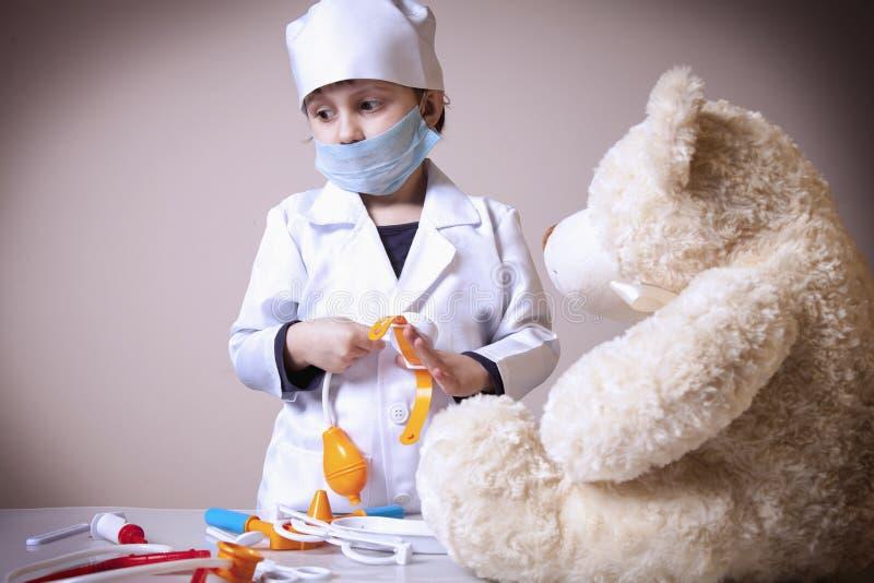 扮演有玩具熊的逗人喜爱的小孩女孩医生 免版税库存图片