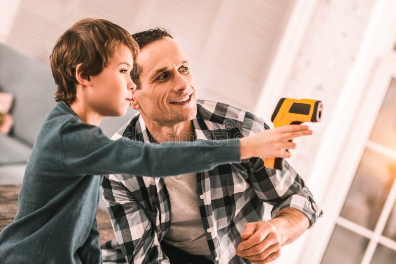扮演有胶水枪的爱的负责任的父亲和有想象力的儿子间谍 免版税库存照片