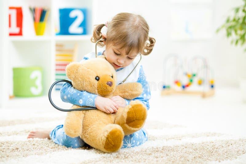 扮演有长毛绒玩具的逗人喜爱的小女孩医生在 库存图片
