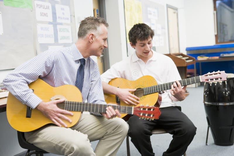 扮演男小学生教师的吉他 图库摄影