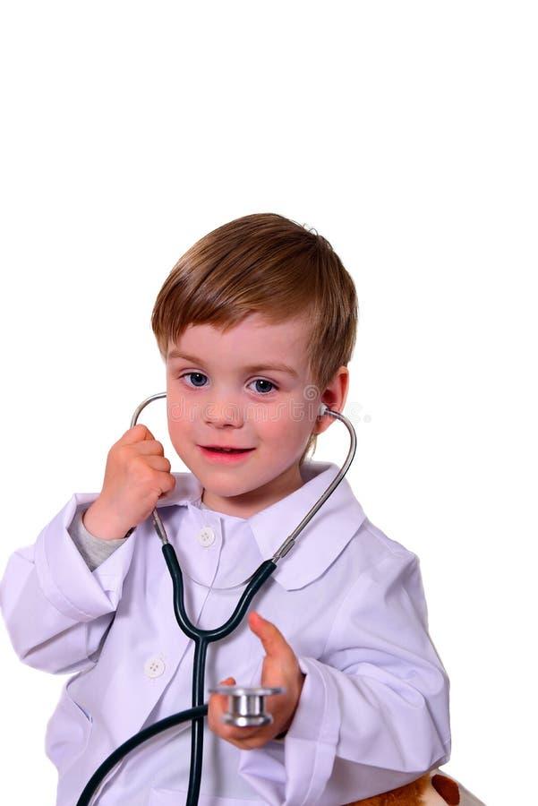 扮演医生的逗人喜爱的微笑的男孩画象  查出在白色 库存图片