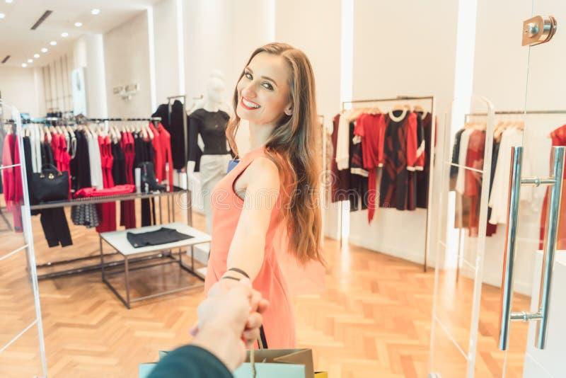 扯拽她的人的妇女塑造购物在精品店或商店 库存图片