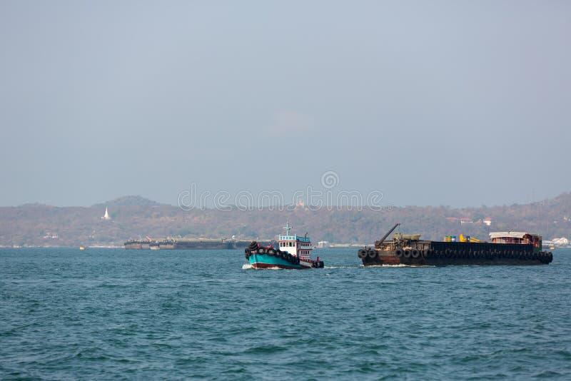 扯拽巨大的撒粉瓶船的小拖曳的拖轮在海 钻井的产业在海洋 背景的图象, 库存照片