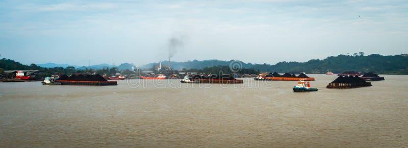 扯拽煤炭的驳船拖轮交通在Mahakam河,印度尼西亚 库存照片