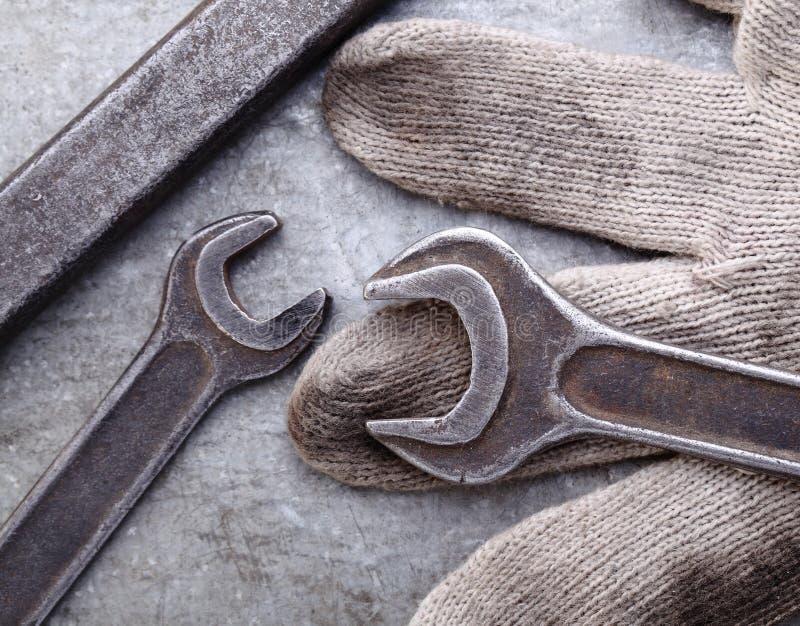 扳手和手套在金属背景 库存图片