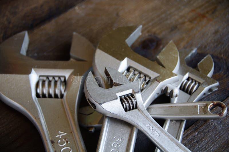 扳手或可调扳手在木后面地面,基本的手工具 图库摄影
