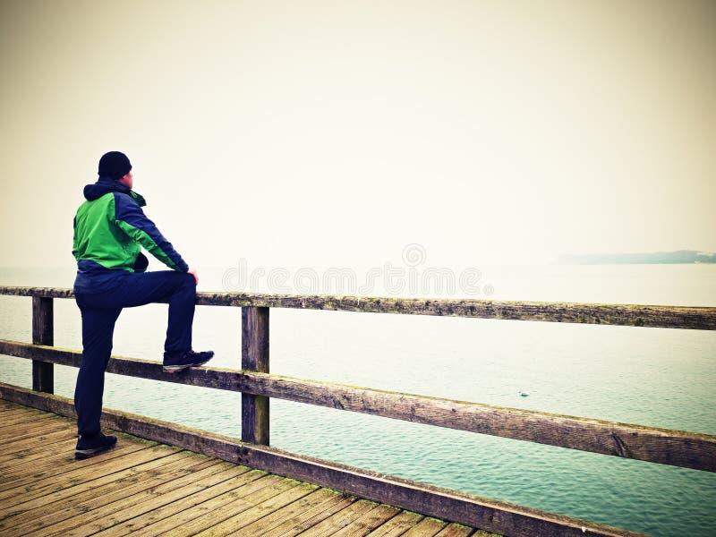 扶手栏杆的,在海码头的秋天有薄雾的早晨单独人 压抑 库存照片