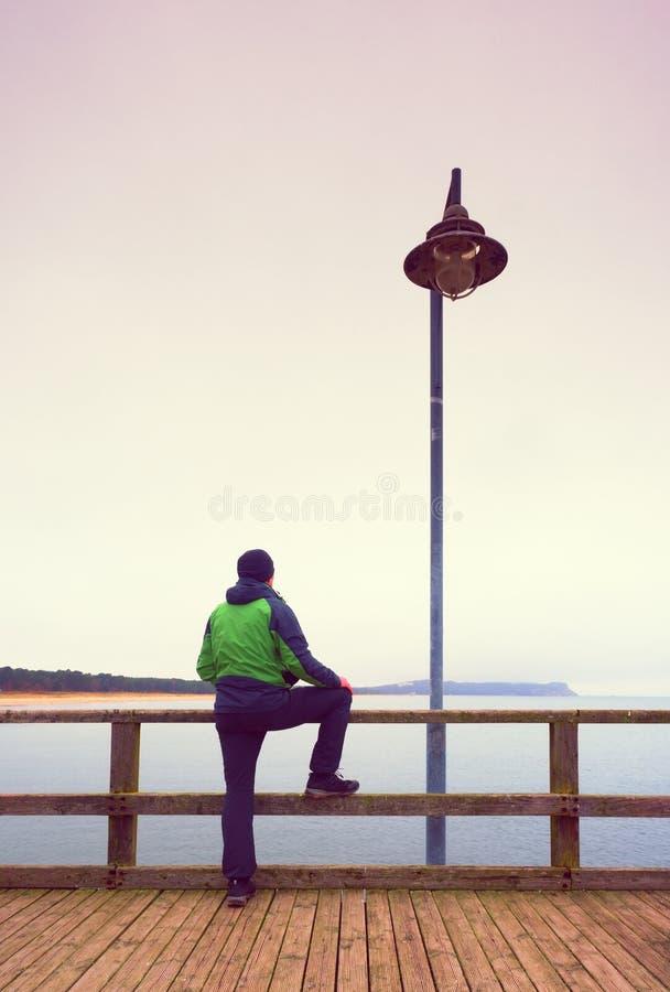 扶手栏杆的,在海码头的秋天有薄雾的早晨单独人 压抑 免版税图库摄影