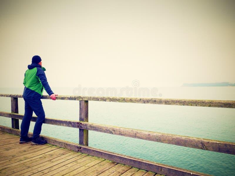 扶手栏杆的,在海码头的秋天有薄雾的早晨单独人 压抑 免版税库存图片