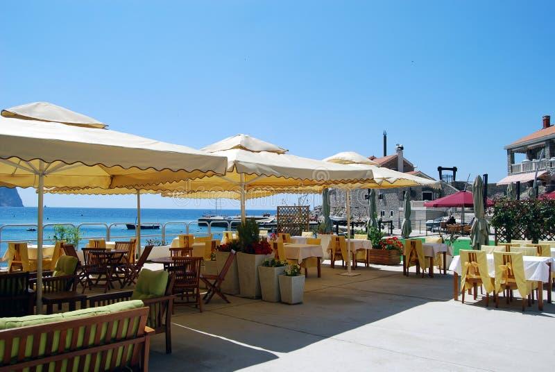扶手椅子使咖啡馆热午间遮阳伞表靠岸下 库存图片