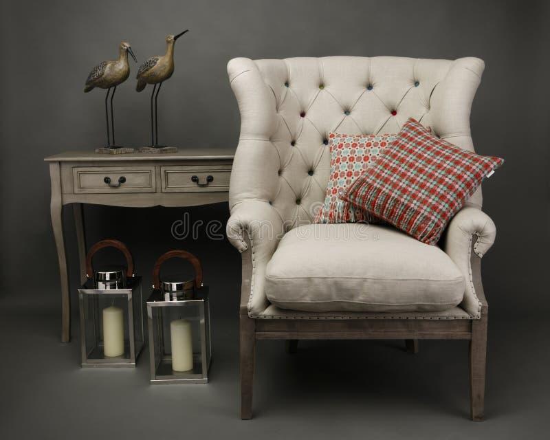 扶手椅子和2个坐垫与旁边桌在灰色背景 图库摄影