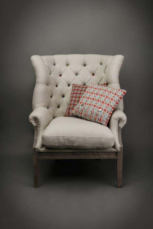 扶手椅子和2个坐垫在灰色背景 库存照片