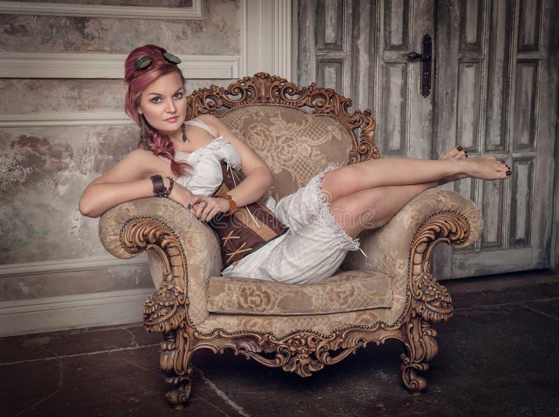 扶手椅子的美丽的steampunk妇女 免版税库存图片