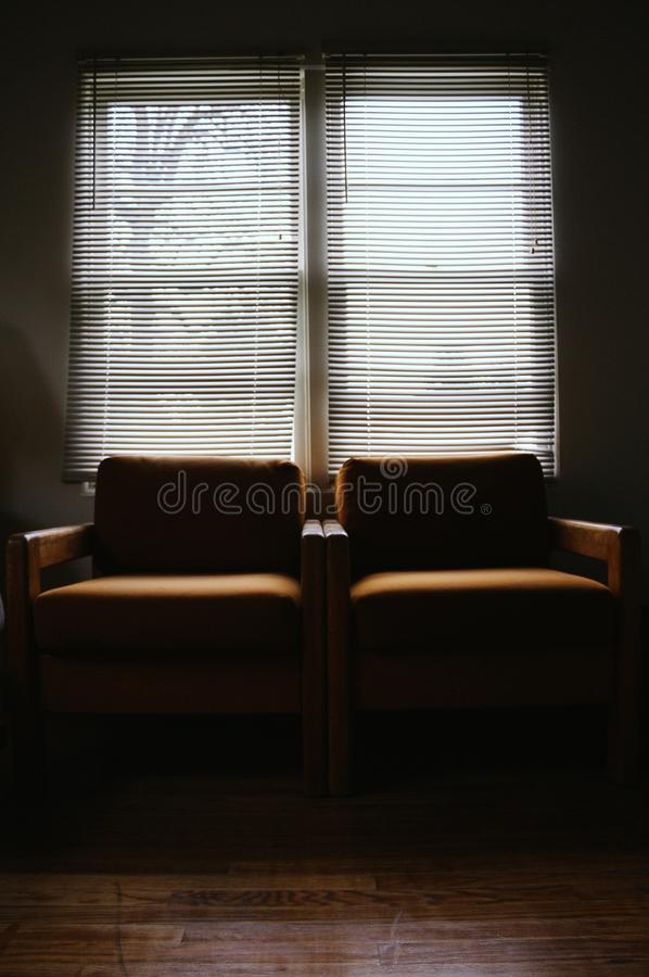 扶手椅子紧挨着在有一个大窗口的一个暗室 库存照片