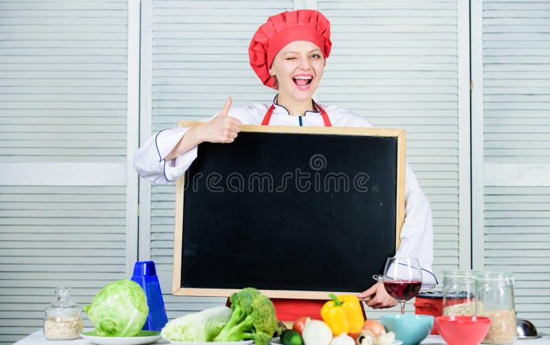 批准您的广告 打手势与空的黑板的可爱的妇女赞许 主要类在烹饪学校 重要资料 库存照片