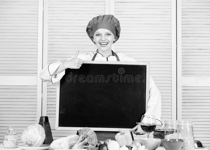 批准某事 打手势与空白的黑板的逗人喜爱的妇女赞许 首要厨师教学在烹饪学院 ?? 图库摄影