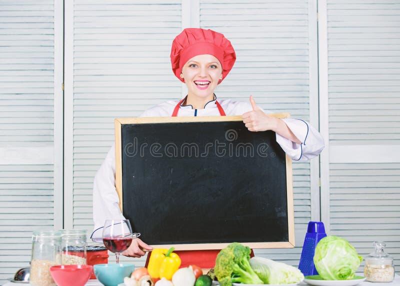 批准某事 打手势与空白的黑板的逗人喜爱的妇女赞许 首要厨师教学在烹饪学院 ?? 库存照片