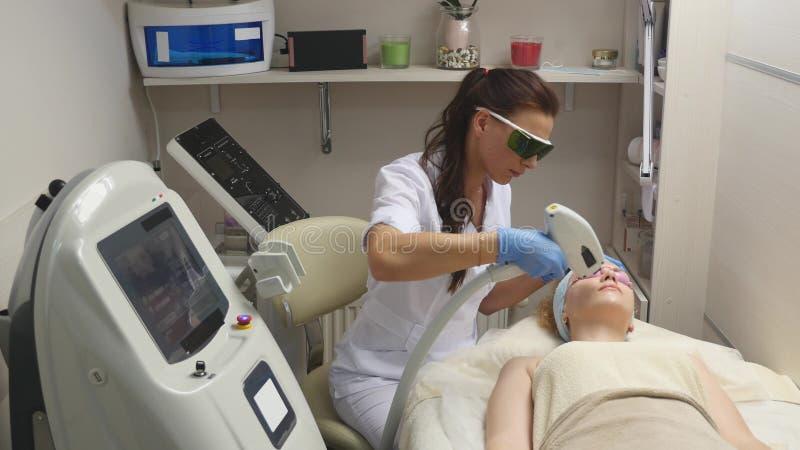 批评执行分数皮肤激光治疗的医生或治疗师射击复出和使a充满活力 图库摄影