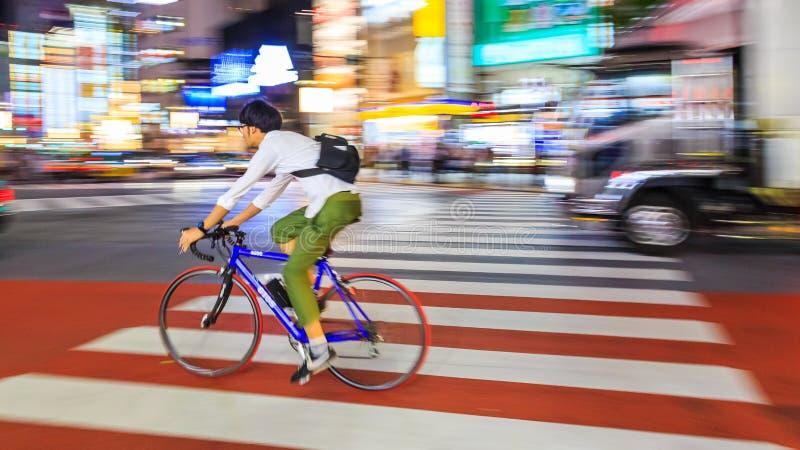批评未认出的人骑马自行车的摄影夜在涩谷广场 那个wor 免版税库存图片
