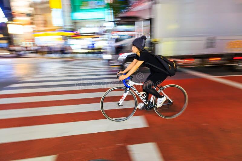 批评未认出的妇女骑马自行车的摄影夜在涩谷广场 那个w 库存图片