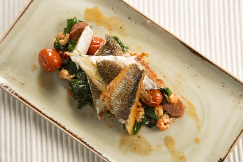 批评油煎的鲈鱼用小龙虾、加调料的口利左香肠、婴孩菠菜&西红柿 免版税图库摄影