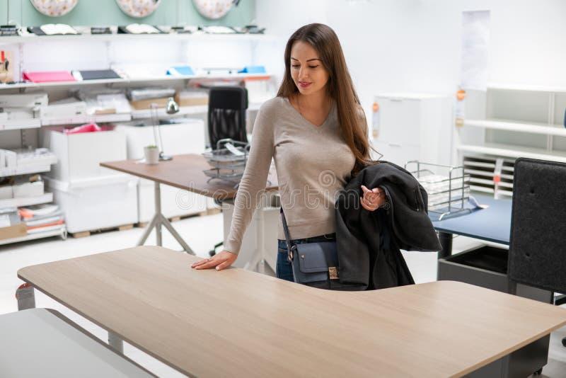 找到的年轻美女新的家具,木桌 免版税图库摄影