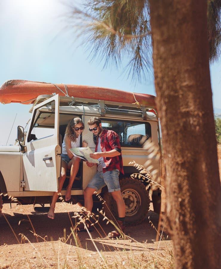 寻找在地图的愉快的年轻夫妇方向 库存照片