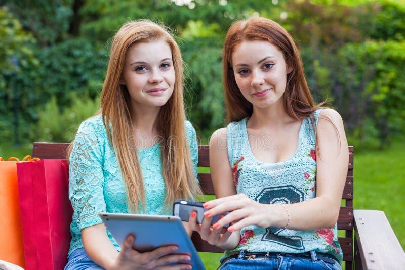 寻找新的销售的两个相当女孩使用片剂 库存照片