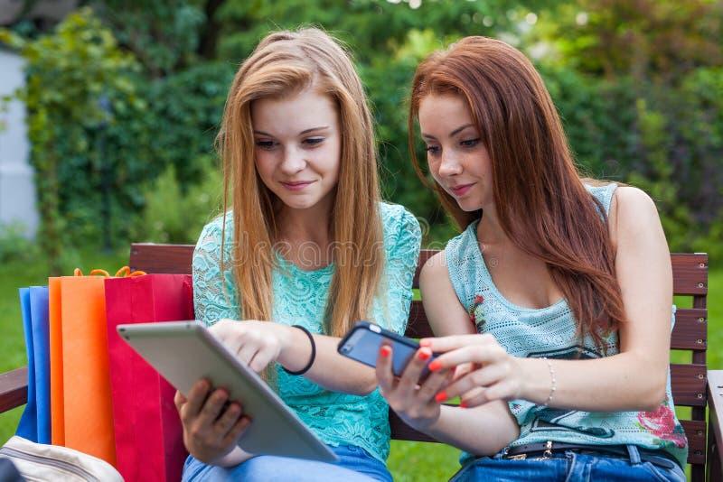 寻找新的销售的两个相当女孩使用片剂 免版税库存图片