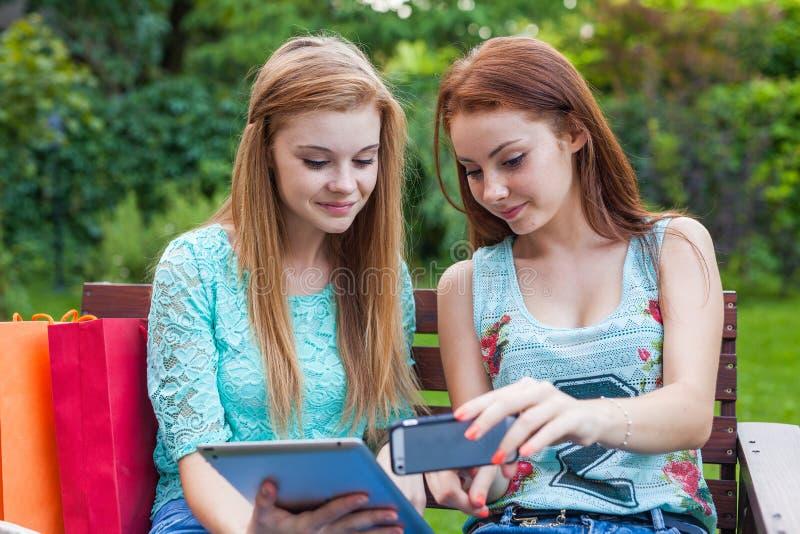 寻找新的销售的两个相当女孩使用片剂 库存图片