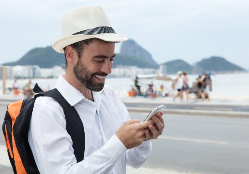 寻找正确的方式的笑的游人在电话 免版税库存图片