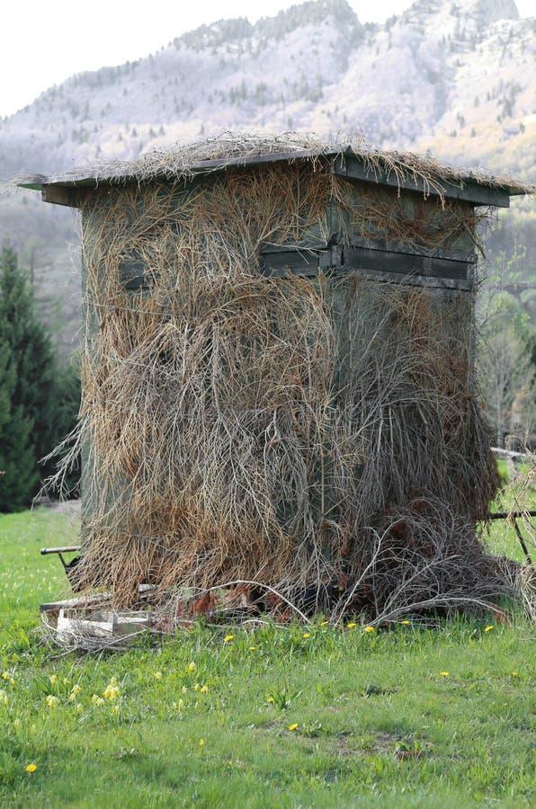 寻找的被伪装的小屋在山 免版税库存图片