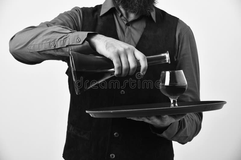 承办酒席和服务概念 葡萄酒绒面革皮革背心的男服务员倒刻痕或白兰地酒 图库摄影