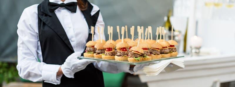 承办酒席服务 运载开胃菜的盘子侍者 室外党用手抓食物,微型汉堡,滑子 免版税库存图片