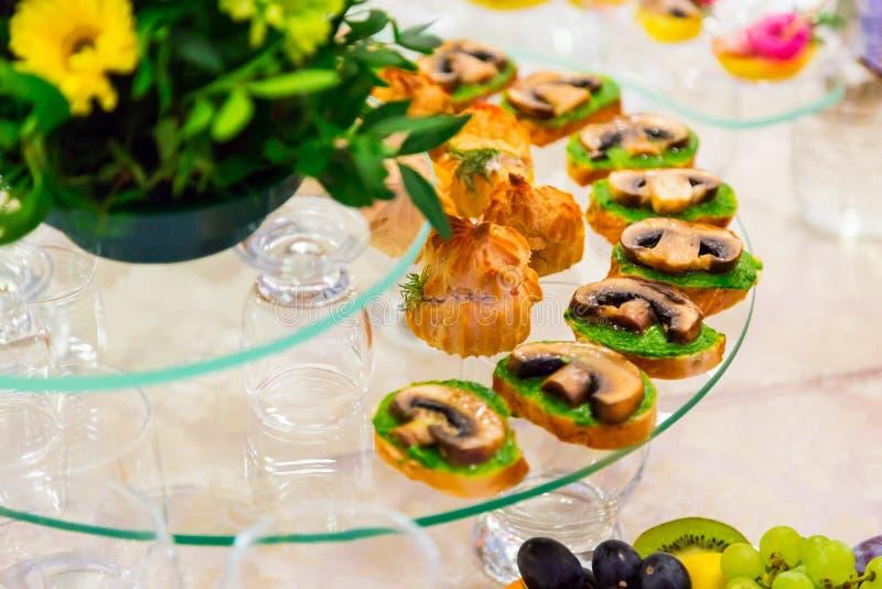 承办酒席 在自助餐的纤巧 三明治用蘑菇 服务的表 免版税库存图片