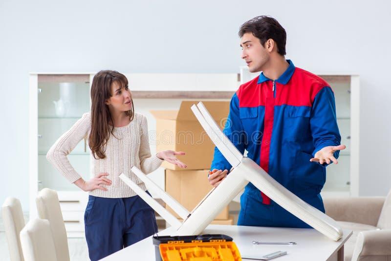 承包商安装工聚集的家具在妇女监督下 免版税库存图片