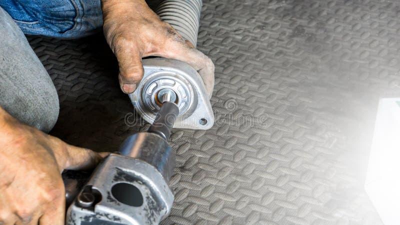 技工人seting的震动的接近的手吸收体的汽车在自动车库和拷贝空间的停止服务的 库存照片